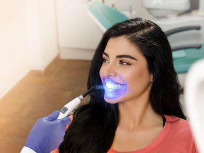 Gorgeous young woman UV lamp teeth whitening treatment